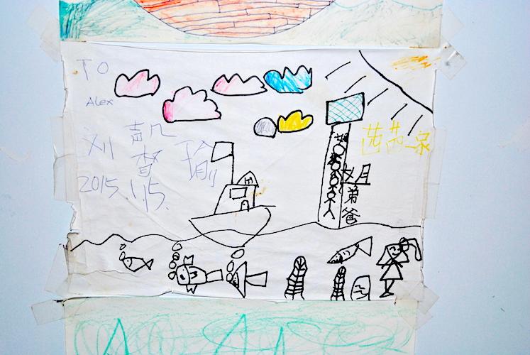 Kjøleskapet er dekket med tegninger fra barn fra hele verden, som denne fra Kina.